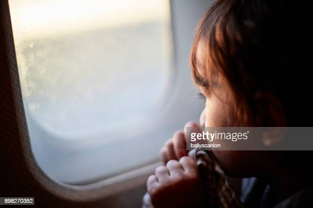 Young Boy Looking Out Of Airplane Window