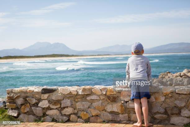young boy looking out over the sea - overberg stock pictures, royalty-free photos & images