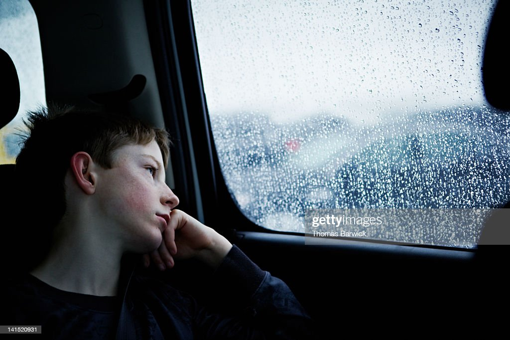 Young boy looking out rainy car window : Stock Photo