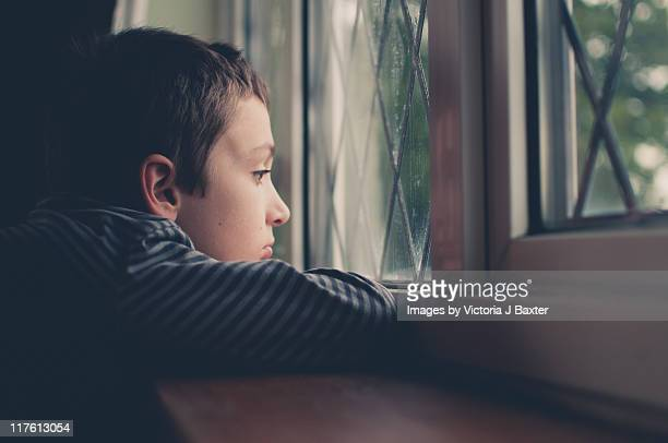 Young boy looking out window on rainy day
