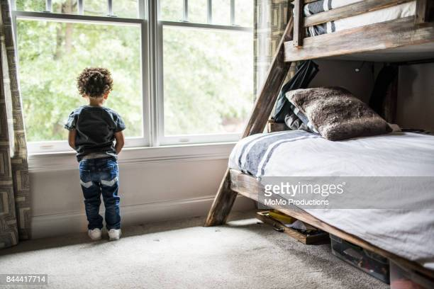 Young boy (2yrs) looking out window