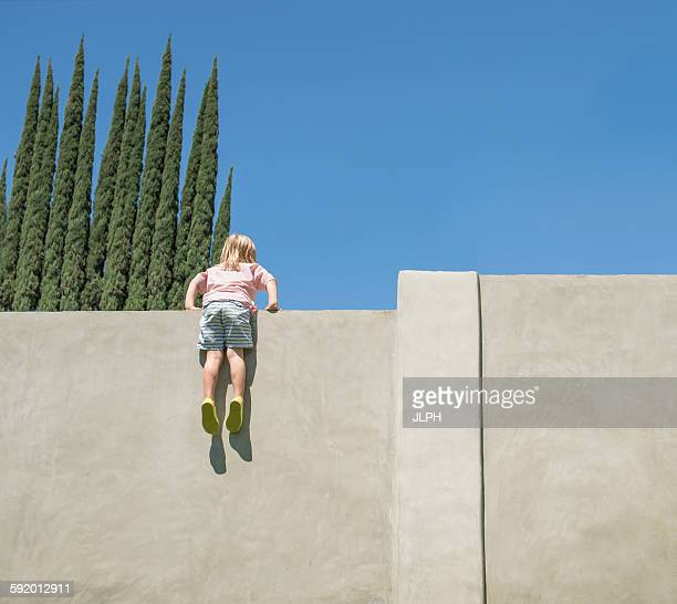 Young boy looking over tall wall, feet dangling, rear view