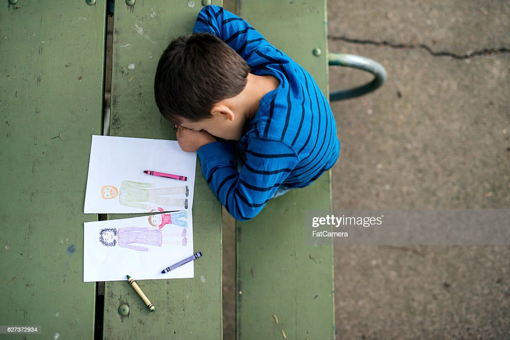Young boy looking sad at drawing of a broken family : Stock Photo