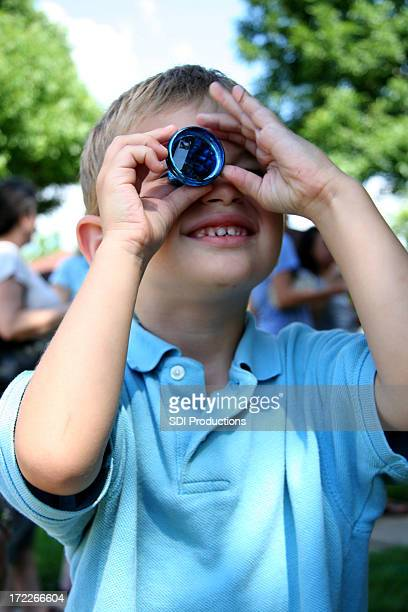 Young Boy Looking Through A Toy Kaleidescope