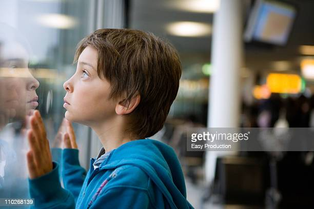 young boy looking through a window - bewondering stockfoto's en -beelden