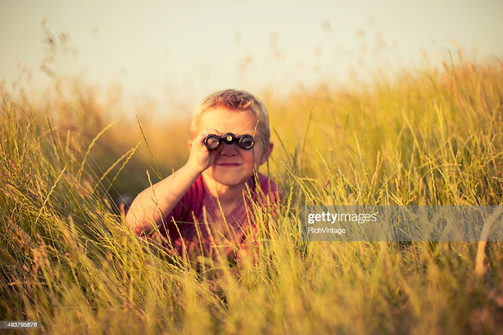 Young Boy Looking Through Binoculars Hiding in Grass : Stock Photo