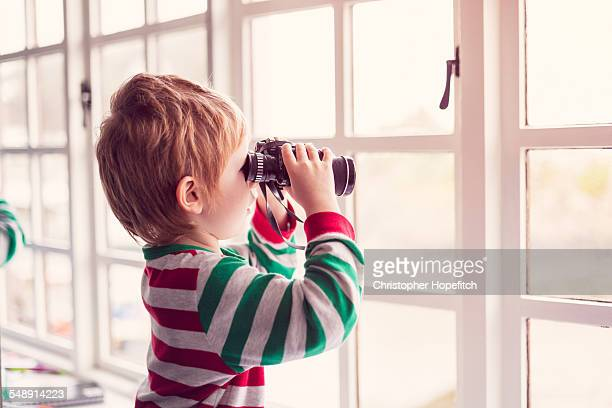 Young boy looking through binoculars