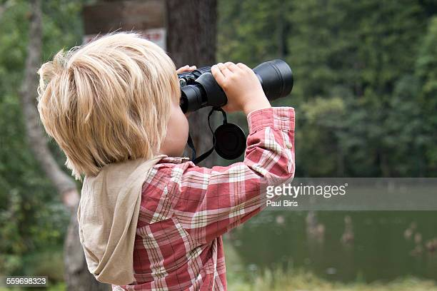 Young boy looking through binoculars