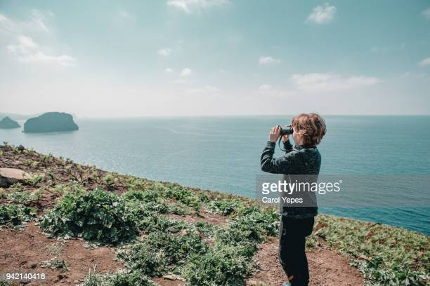 young boy looking through binoculars - stalker person stock photos and pictures