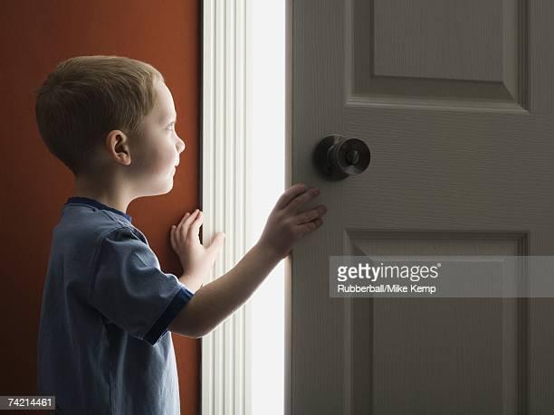 young boy looking through doorway - solo un bambino maschio foto e immagini stock