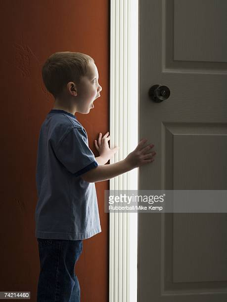 Young boy looking through doorway with mouth open