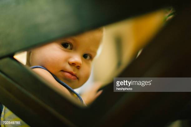 young boy looking through gap in furniture - heshphoto ストックフォトと画像