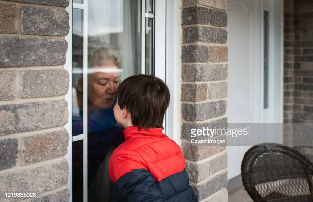 young boy looking through window at grandma during covid 19 pandemic. - visit stock pictures, royalty-free photos & images