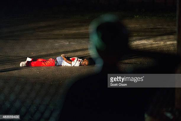 Young boy looks at a man with gunshot wounds lying in a parking lot after a shoot out with police along West Florissant Street during a demonstration...