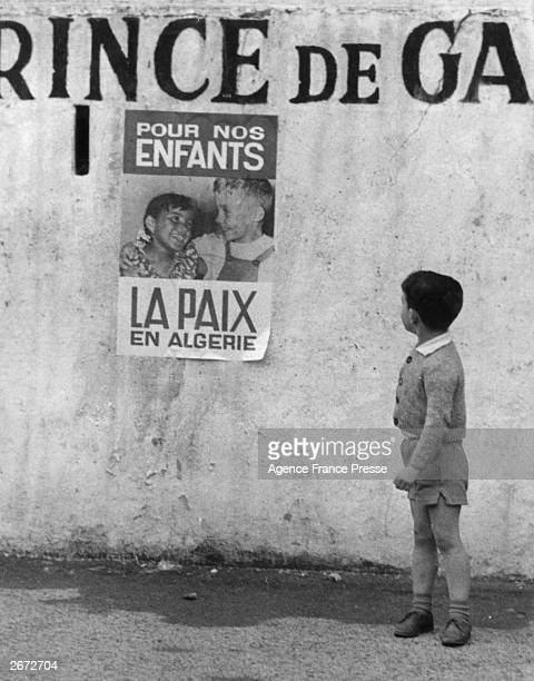 A young boy looks at a poster calling for peace in Algeria which shows a boy and a girl of seemingly different ethnic groups happily interacting...