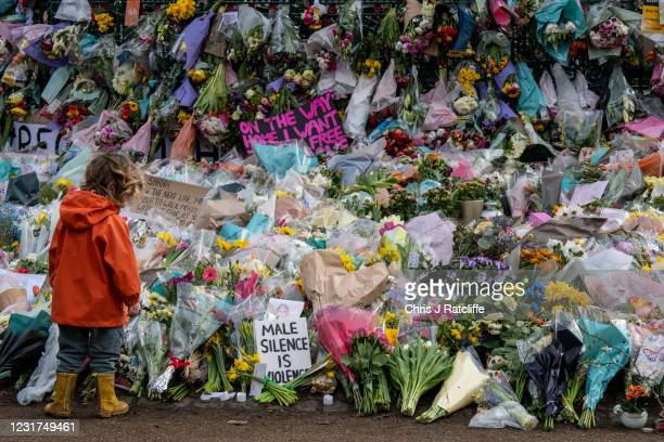 Young boy looks at floral tributes left at Clapham Common bandstand where people continue to pay their respects to Sarah Everard on March 16, 2021 in...