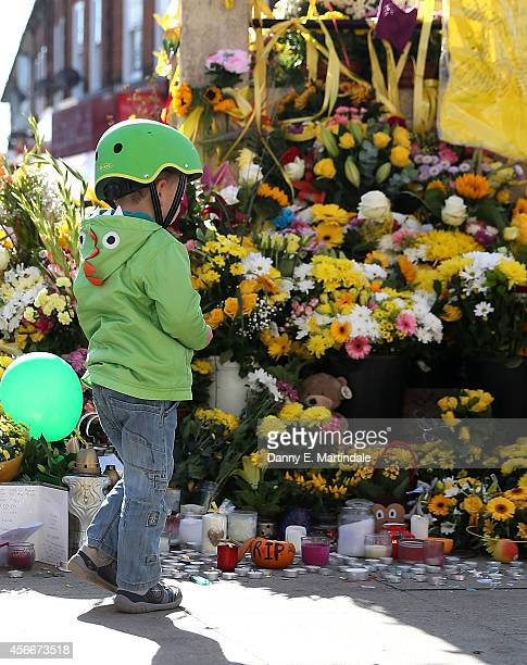 A young boy looks at flowers left at the Hanwell clock tower in memory of Alice Gross on October 5 2014 in London England A body believed to be that...