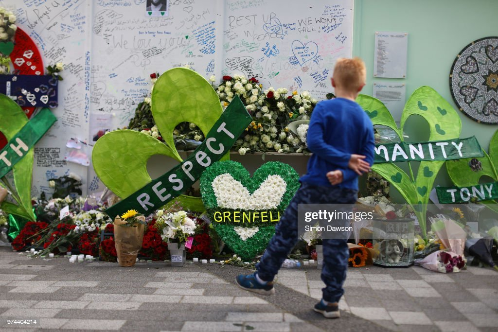 A young boy looks at tributes left at a memorial wall by Grenfell Tower on the one year anniversary of the Grenfell Tower fire on June 14, 2018 in London, England. In one of Britain's worst urban tragedies since World War II, a devastating fire broke out in the 24-storey Grenfell Tower on June 14, 2017 where 72 people died from the blaze in the public housing building of North Kensington area of London.