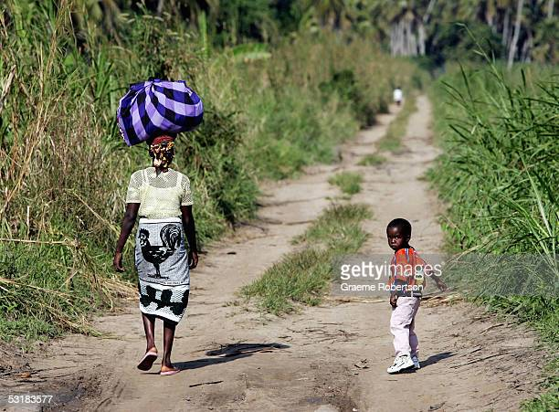 A young boy looks back as his mother walks carrying coconuts on her head along a dirt road on July 2 2005 in Mozambique Since Mozambique's 15year...