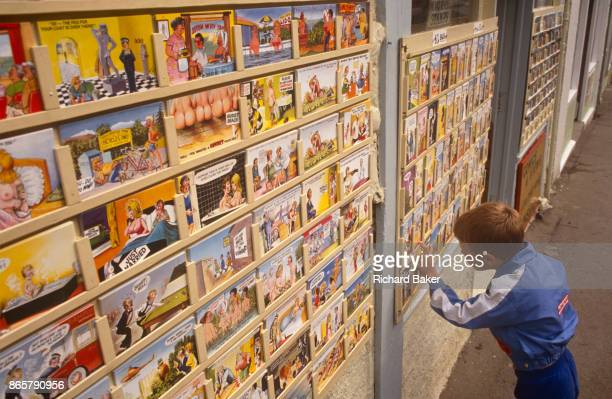 Young boy looks carefully at the many saucy postcards on sale outside a seaside shop, on 19th July 1993, in Scarborough, North Yorkshire, England....
