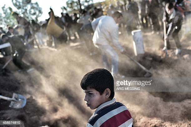 A young boy looks on as he attends the funeral of a Kurdish Women's Protection Unit fighter who died during fighting in the besieged Syrian border...