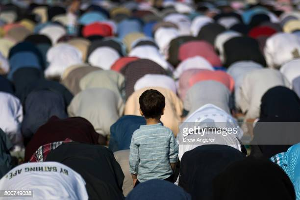 A young boy looks on as Muslims participate in a group prayer service during Eid alFitr which marks the end of the Muslim holy month of Ramadan in...
