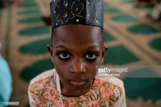 A young boy looks on during a special Jumu'ah prayer service at the Central Mosque in Lagos on February 15 on the eve of Nigeria's presidential...