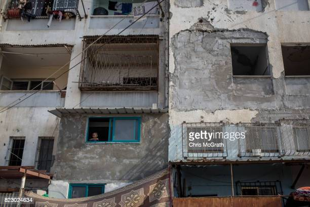 A young boy looks out from his window in the Beit Lahia neighborhood on July 24 2017 in Gaza City Gaza For the past ten years Gaza residents have...