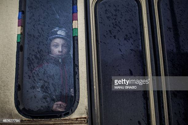 Young boy looks out of the window of a bus before fleeing the Ukrainian city of Debaltseve, in the Donetsk region, on February 1, 2015. Civilians...