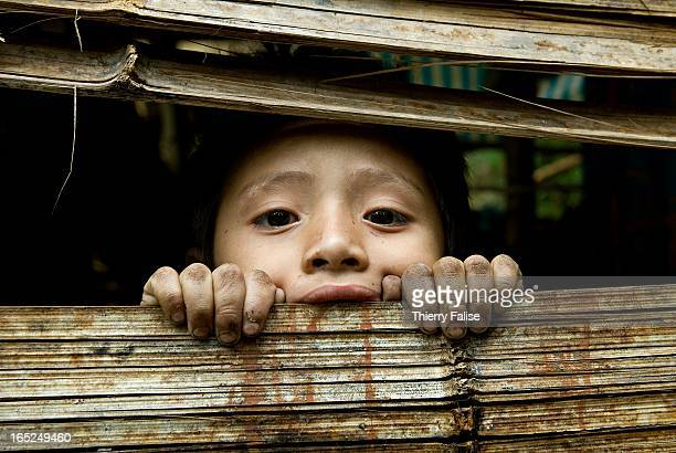 A young boy looks through a hole in the bamboo hut built in the jungle of the Northern Karen State where he lives with his family after being forced...