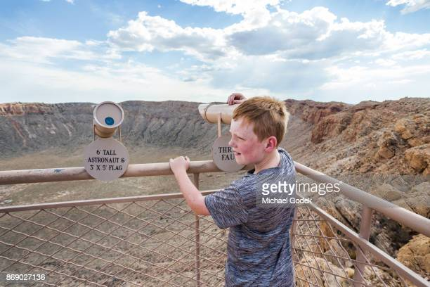 A young boy looks through a telescope at an observation point