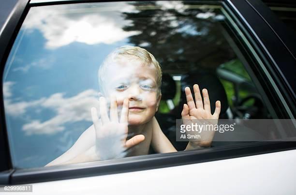 Young boy looks through car window