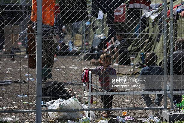 A young boy looks through the fence of the migrant holding camp at the Hungarian border with Serbia on September 12 2015 in Roszke Hungary Migrants...