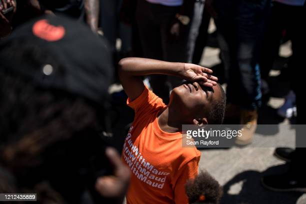 Young boy looks up at the sun as people gather to honor the life of Ahmaud Arbery at Sidney Lanier Park on May 9, 2020 in Brunswick, Georgia. Arbery...