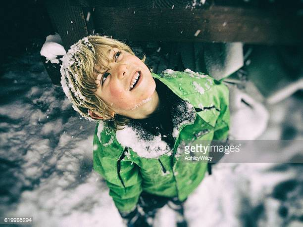 Young boy looks up, watches snow fall