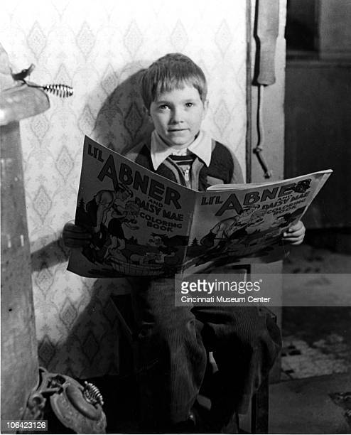Young boy looks up while reading a Li'l Abner coloring book, Cincinnati, OH, mid to late twentieth century.