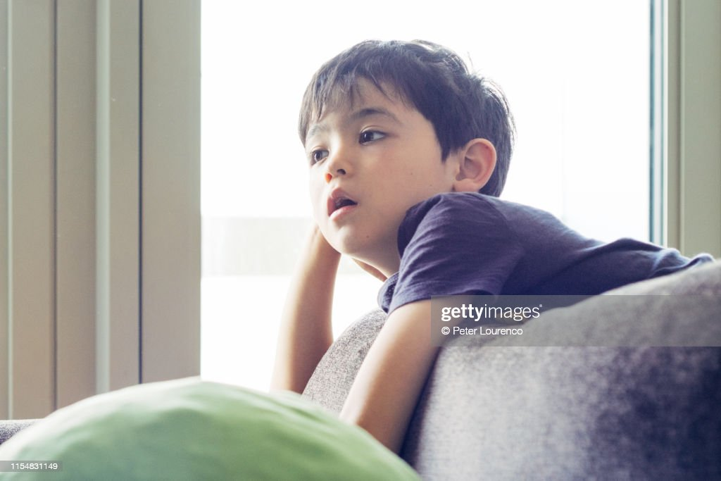 Young boy lounging on sofa : Stock Photo