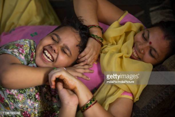 young boy lying down on sofa with his mother - salwar kameez stock pictures, royalty-free photos & images