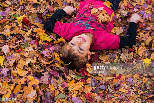 Young boy lying in autumn leaves