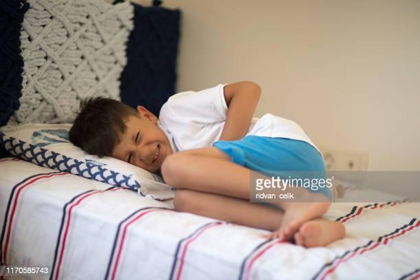腹痛でベッドに横たわる少年 - 男児1人 ストックフォトと画像
