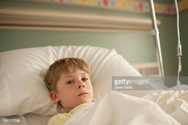 Young boy lying in hospital bed