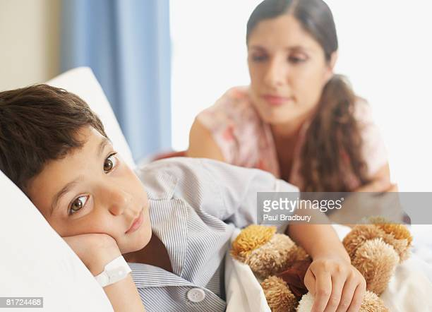 Young boy lying in hospital bed with teddy bear and woman looking over him