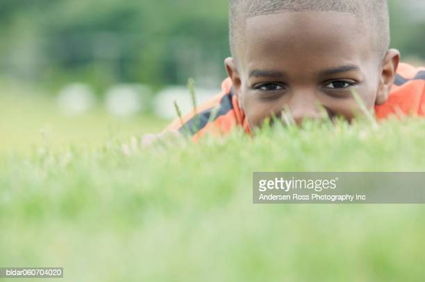 Young boy lying in the grass at a golf course