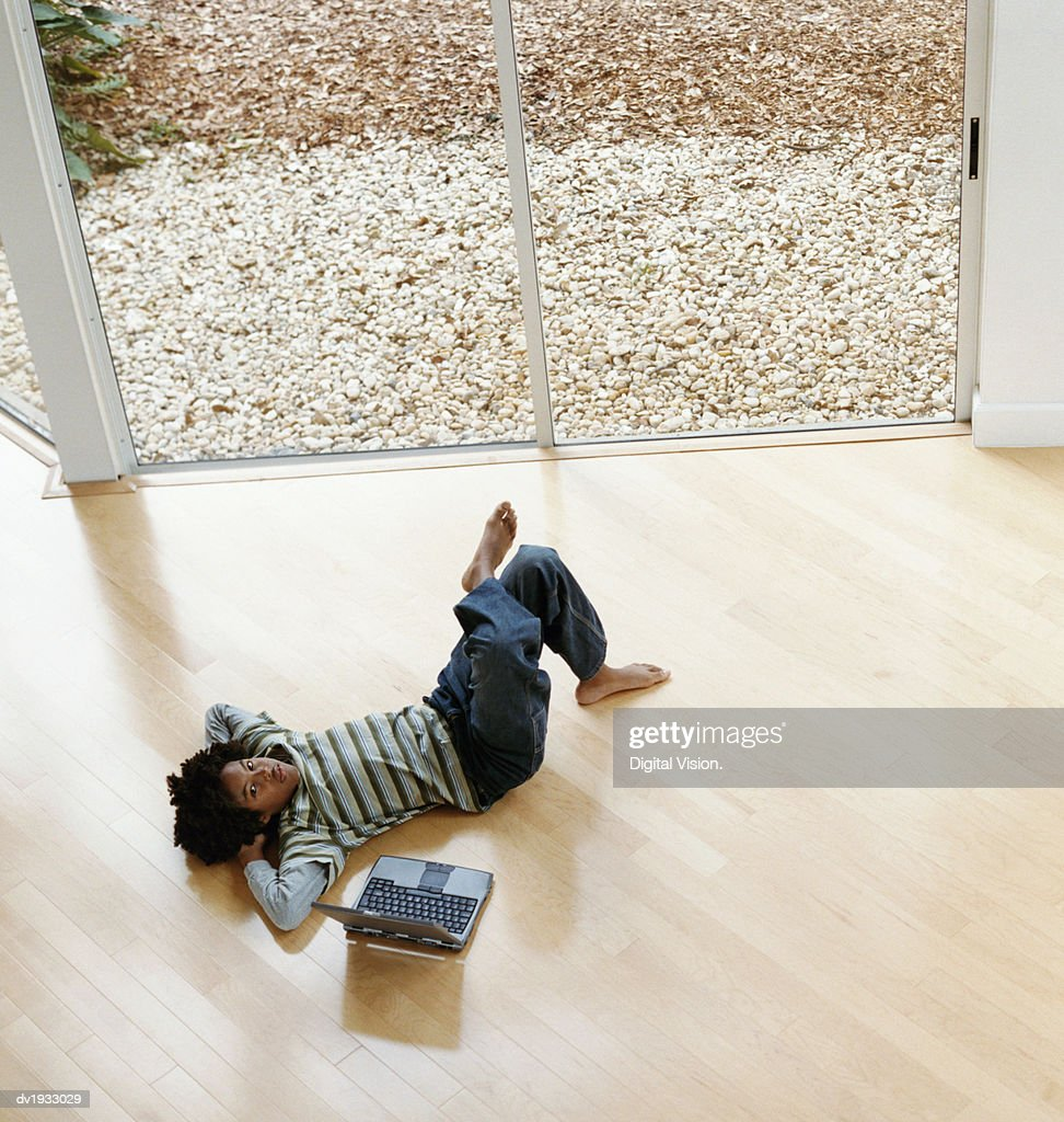 Young Boy Lying on a Wooden Floor Next to a Laptop Computer : Stock Photo