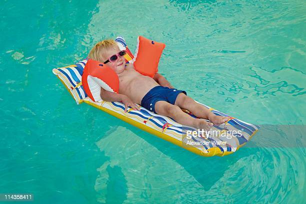 young boy lying on air bed floating in swimming pool