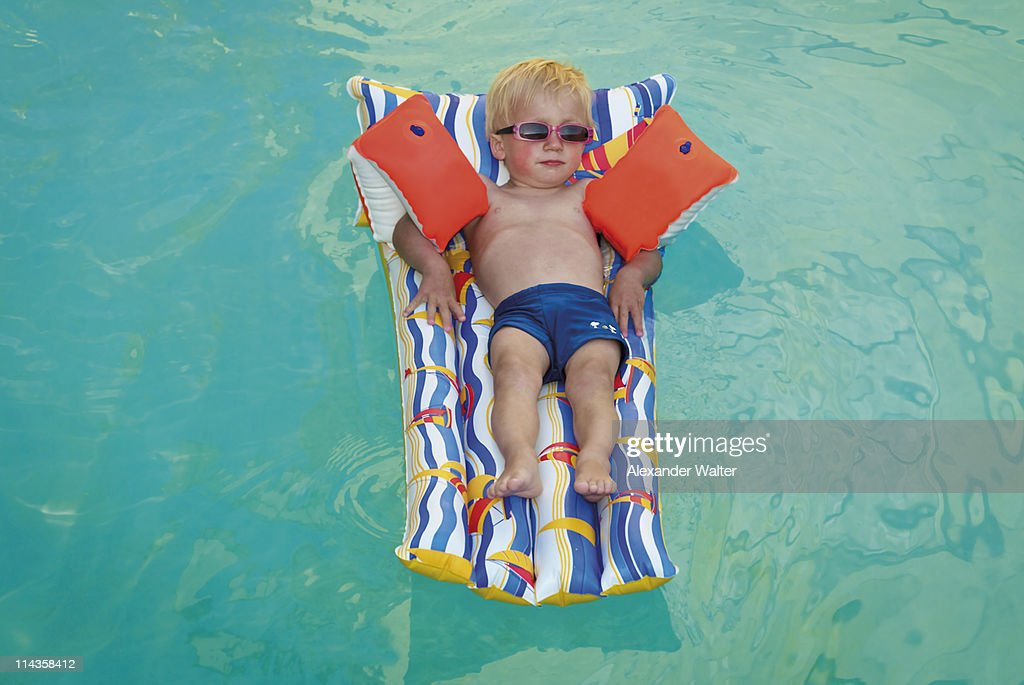 young boy lying on air bed floating in swimming pool picture id