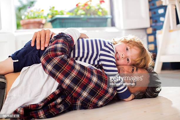 Young boy lying on father on floor