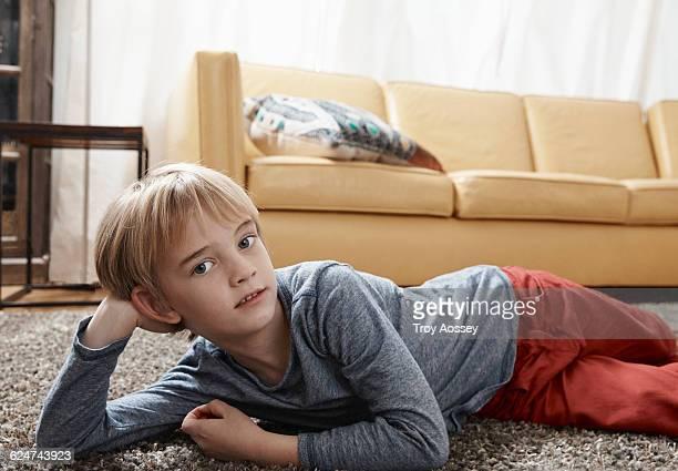 Young boy lying on living room floor.