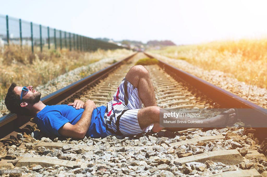 Young boy lying on train tracks : Foto de stock