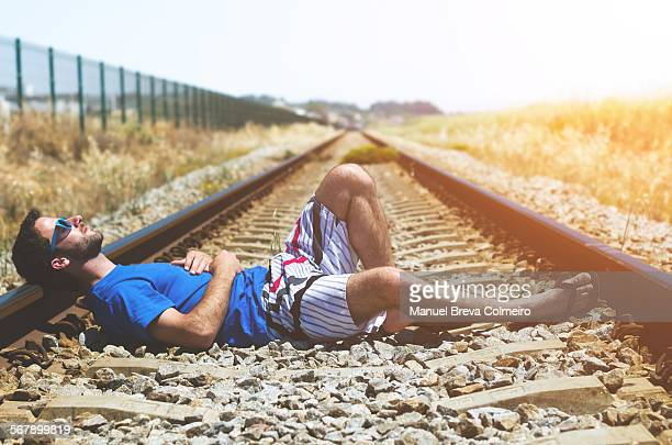 Young boy lying on train tracks